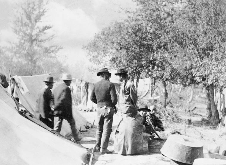 Men stand and crouch in a camp of tents and laundry lines.