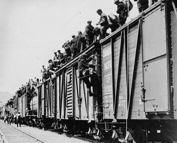 Men cover the roofs of boxcars.