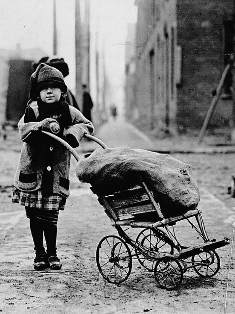 Young girl carting around a bag of coal.