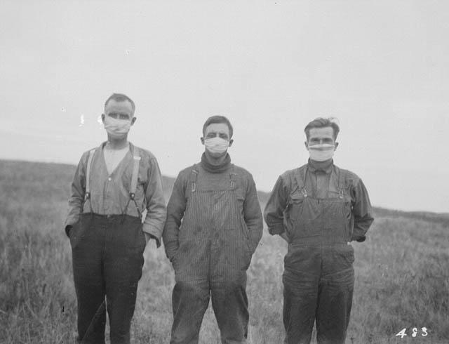 Three men in overalls stand on the prairies, wearing flu masks.