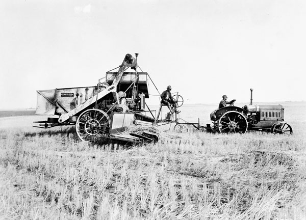 A man drives a tractor, while another works a combine.