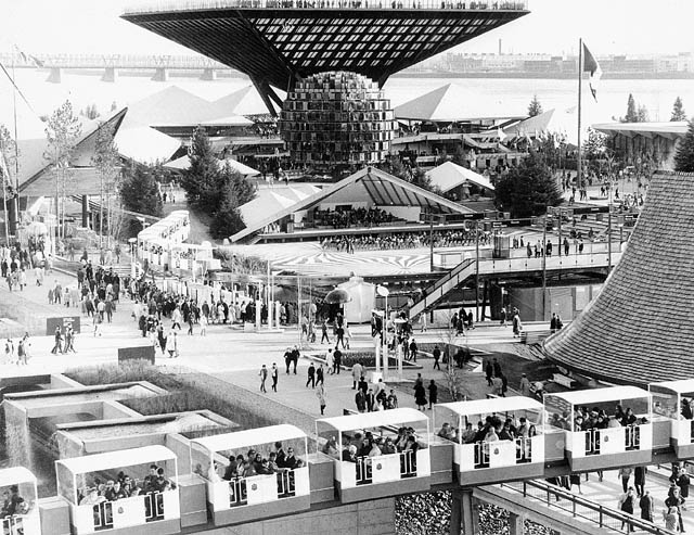 Display buildings with futuristic architecture. A monorail full of passengers is in the foreground.