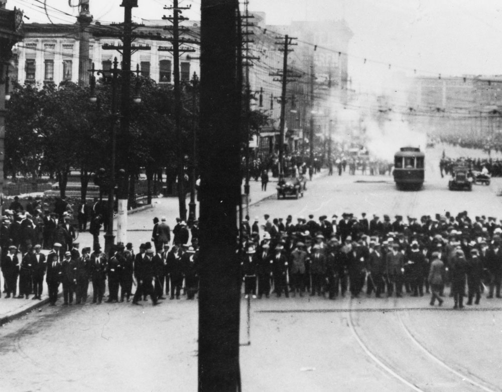 Men form a line and block the street. Many wear white armbands.