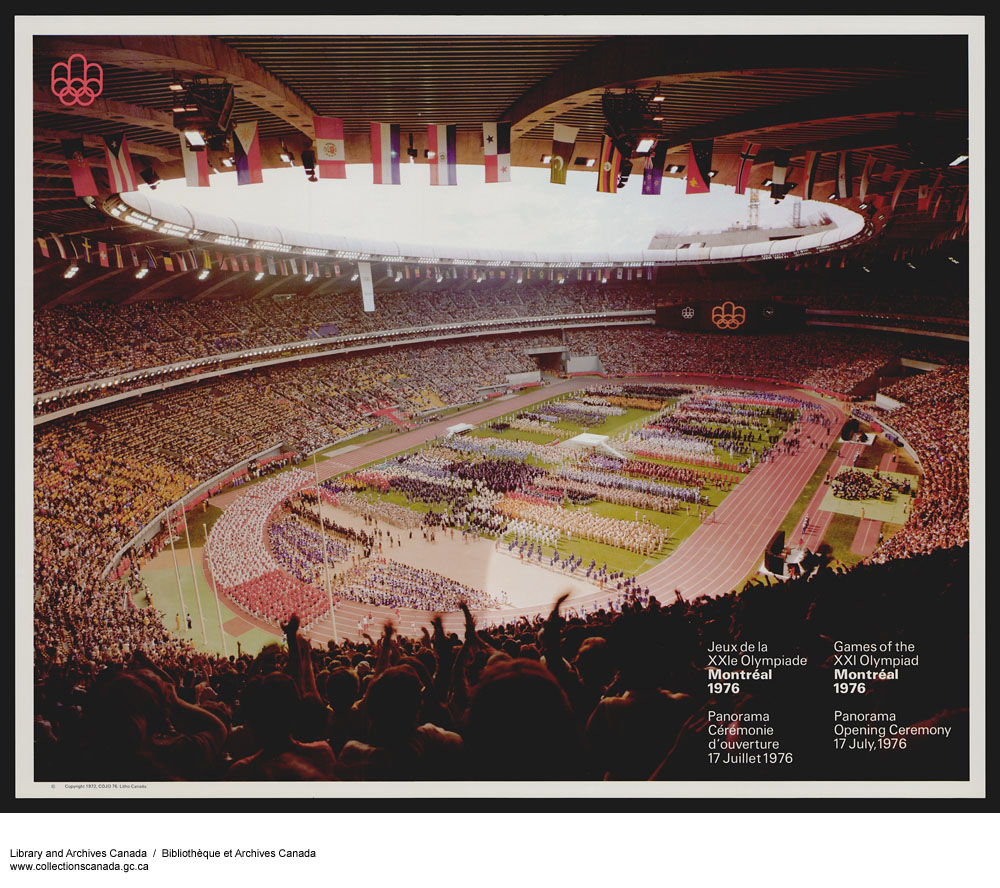 A stadium full of athletes and fans. International flags hang from the open ceiling.