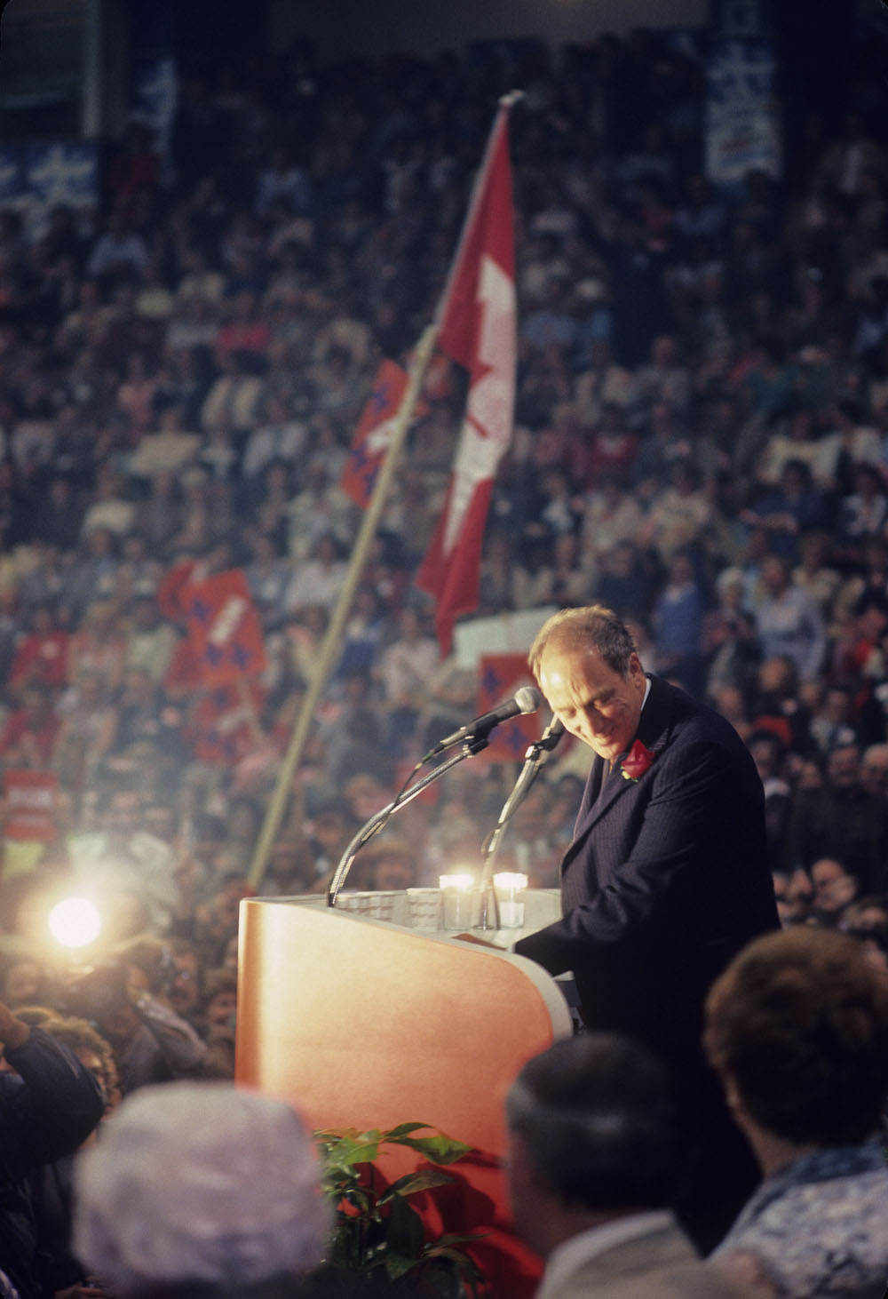 A man standing at a podium ducks his head, smiling. He speaks to a huge crowd.