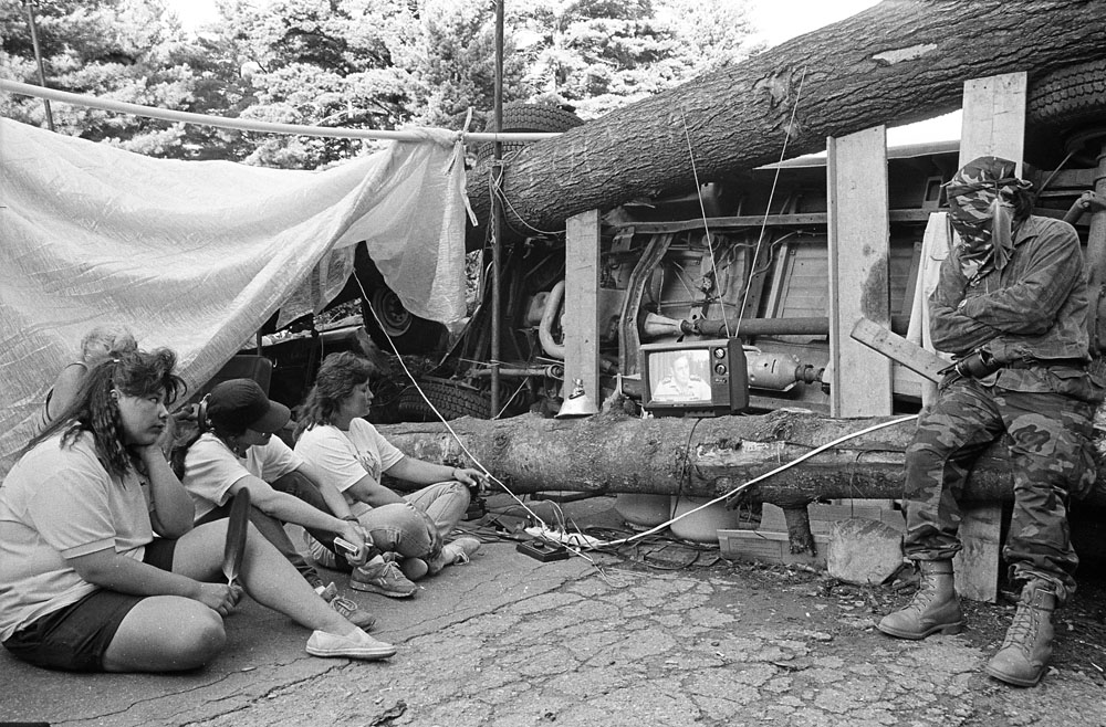 Four people sit outside and watch a small television sitting on a log. One wears camouflage.