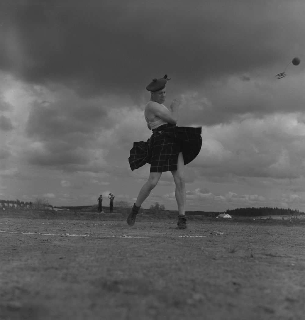 A kilted man standing in a white chalk circle is twisted after throwing a stone, which flies away.