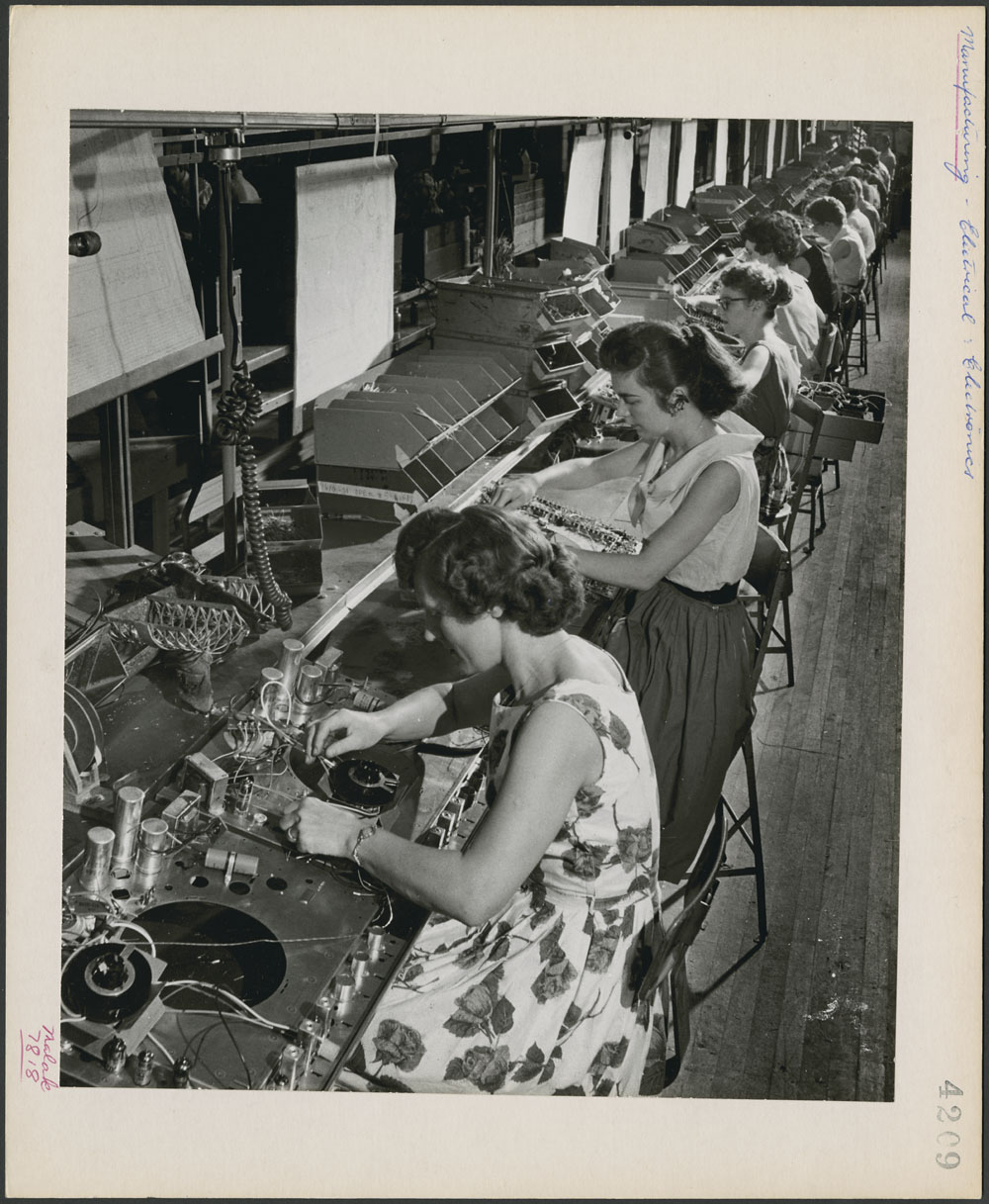 Assembly line of seated women, working on electronics.