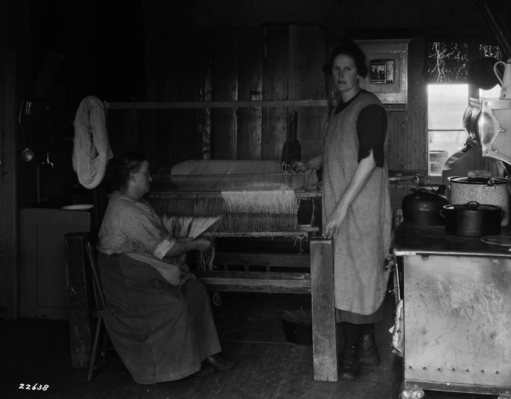 Two women work on a loom in a cramped kitchen.
