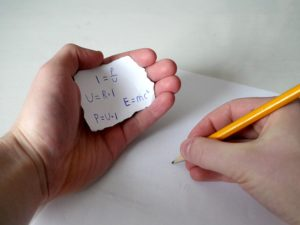 A person taking a test cheats by peaking at the formulas they've copied on a scrap of paper