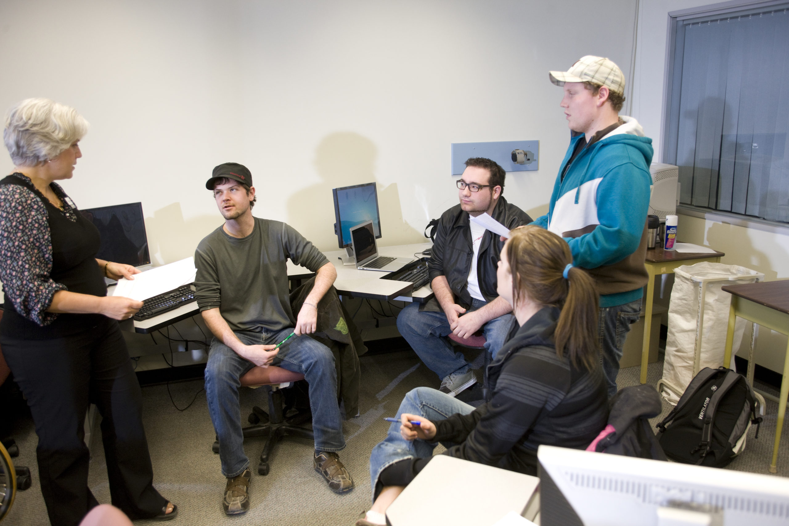 A group of students talking a computer lab