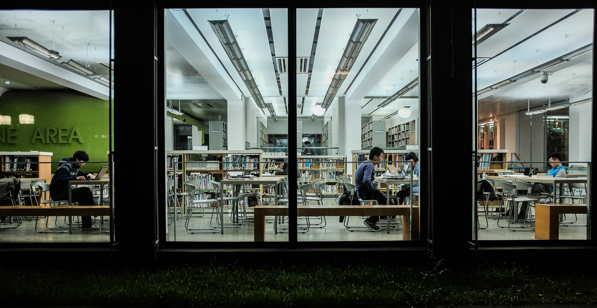 Students studying at large tables in a library late at night
