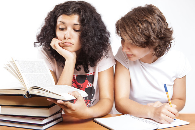 Two people lean over a pile of books. One takes notes.