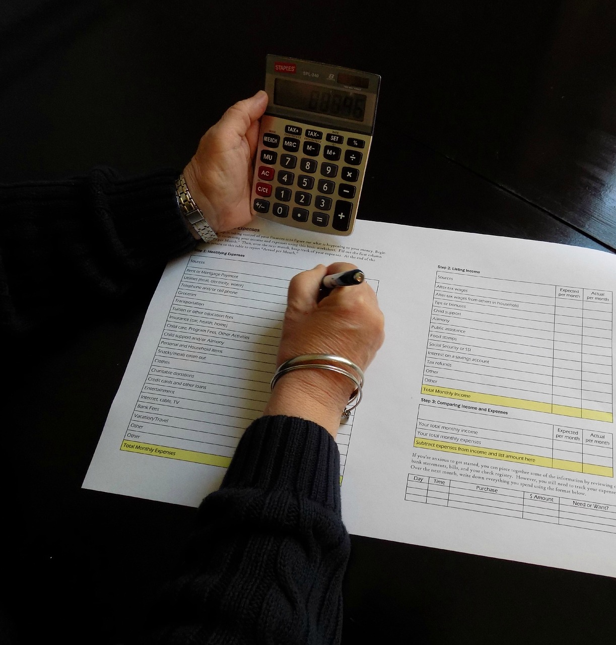 A person calculating their budget with a calculator