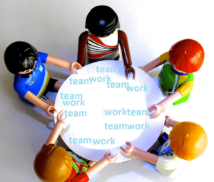 """A group of toys gathered around a table. The table has """"team work"""" written all over it"""