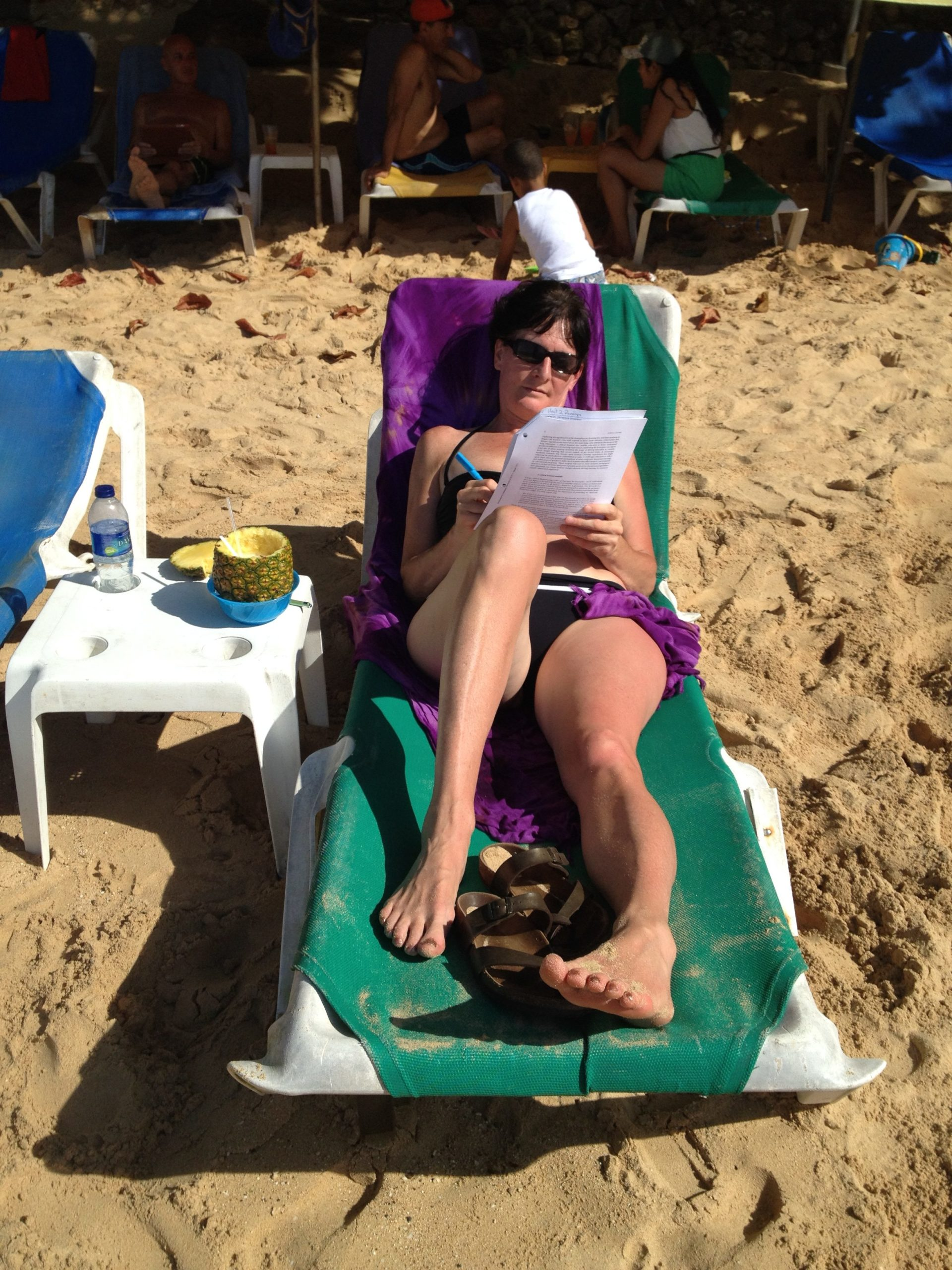 Mary Shier sitting in a lounge chair in her bathing suit on a beach taking notes