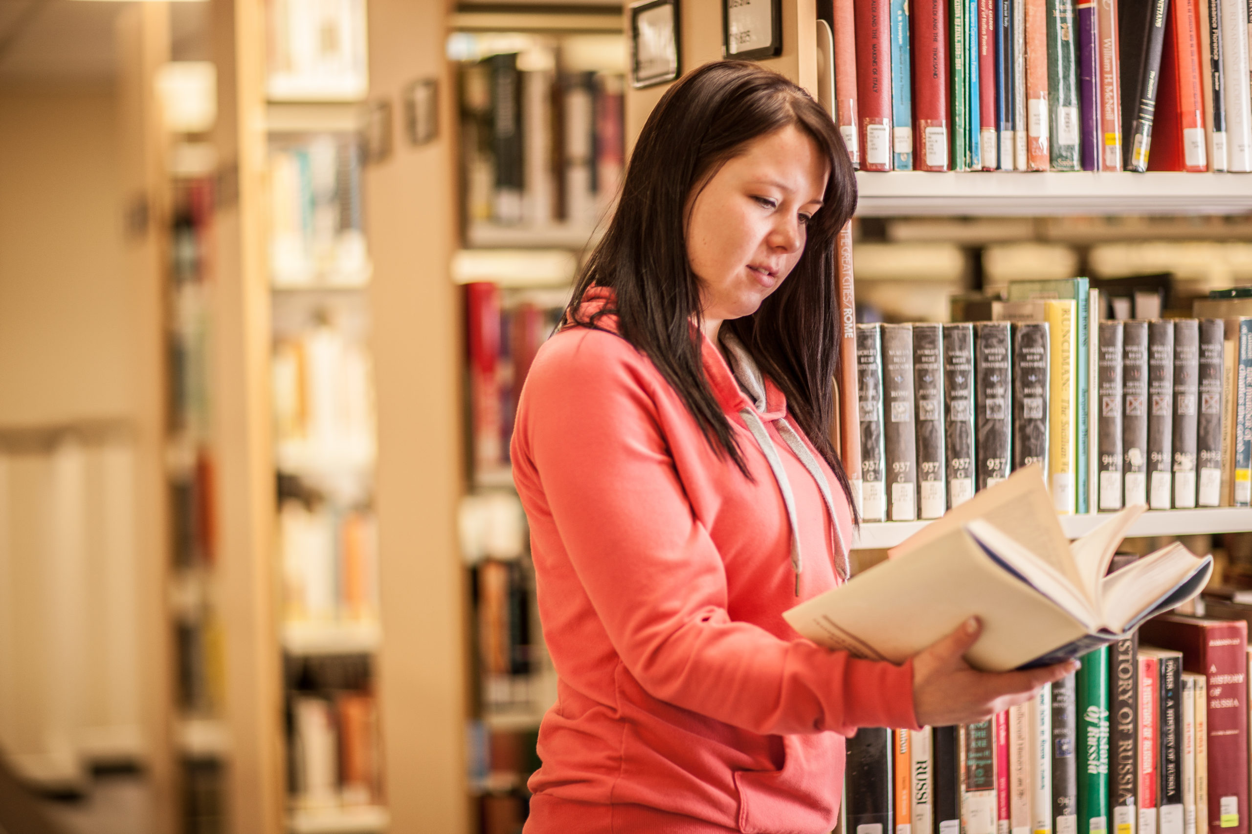 A woman reading a book in the library