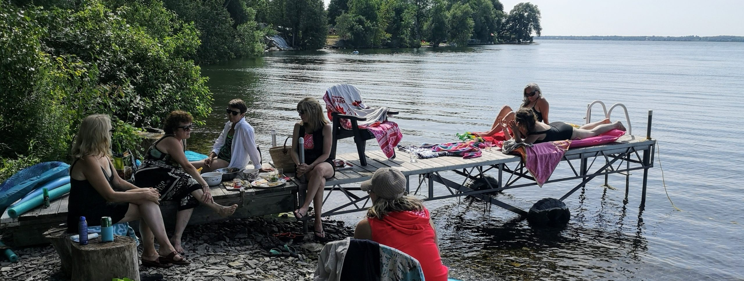 A group of women-friends chatting and hanging out by the lake
