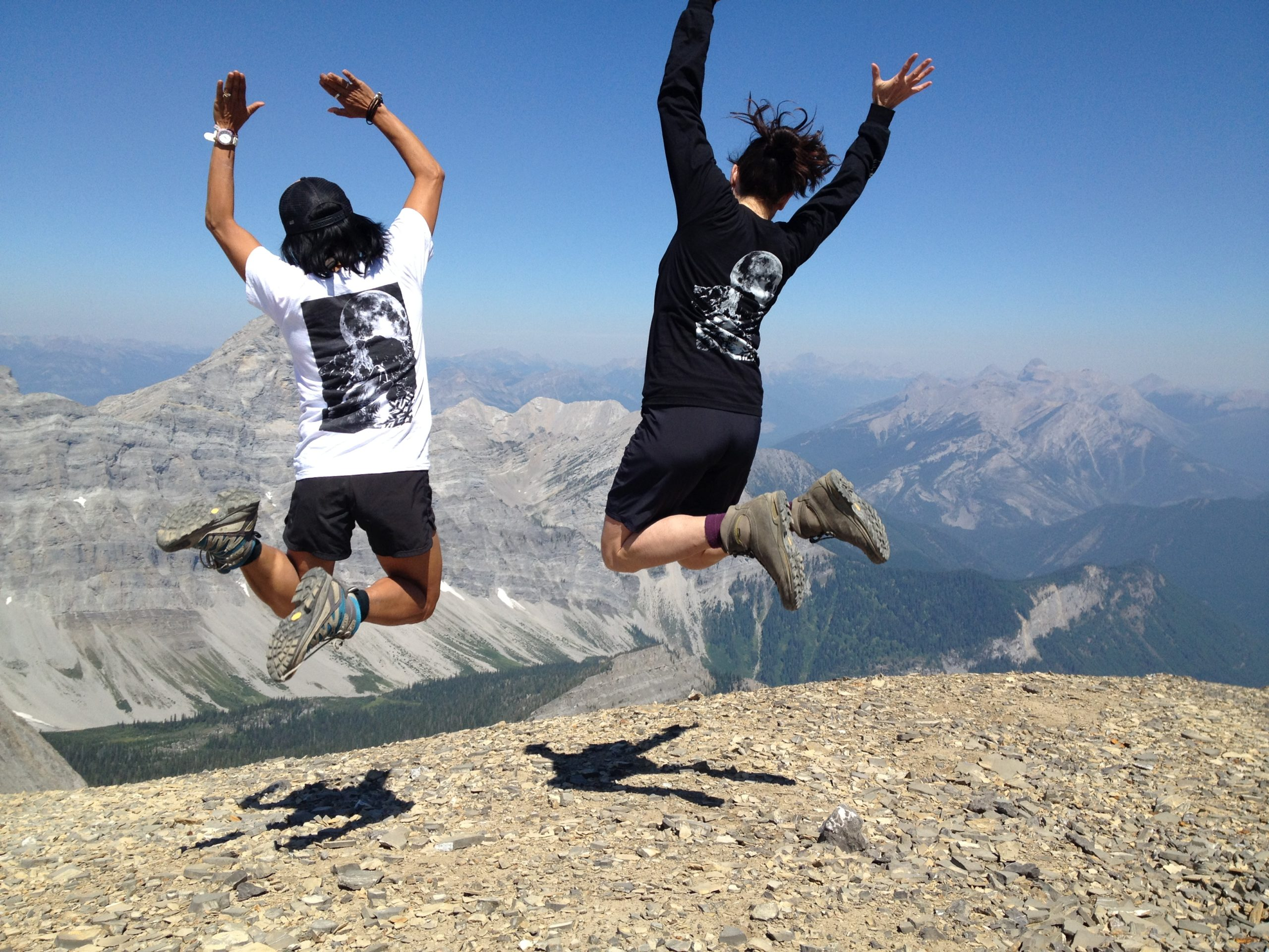 Two people on top of a mountain leaping into the air