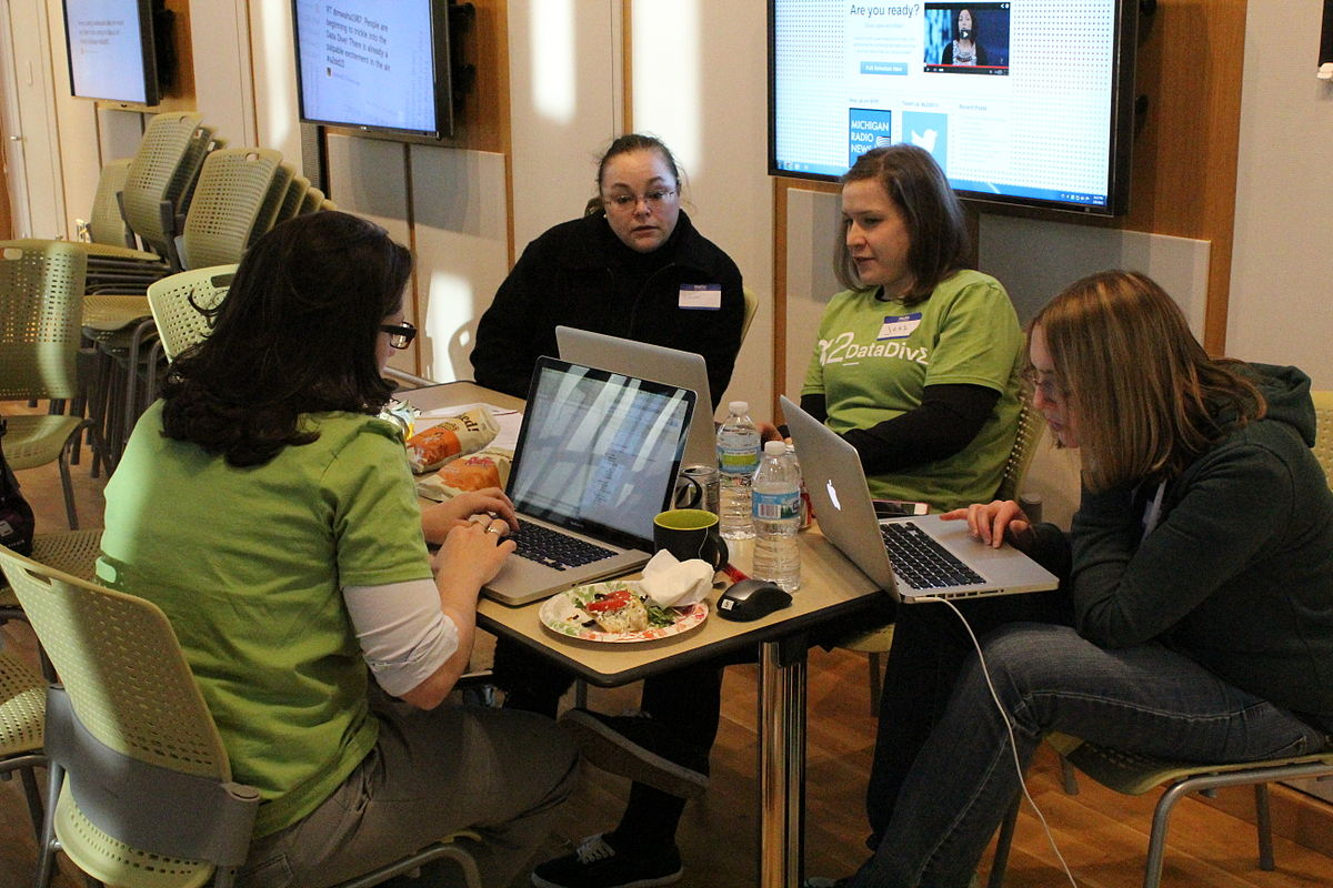 A group of people gathered around a table on laptops.