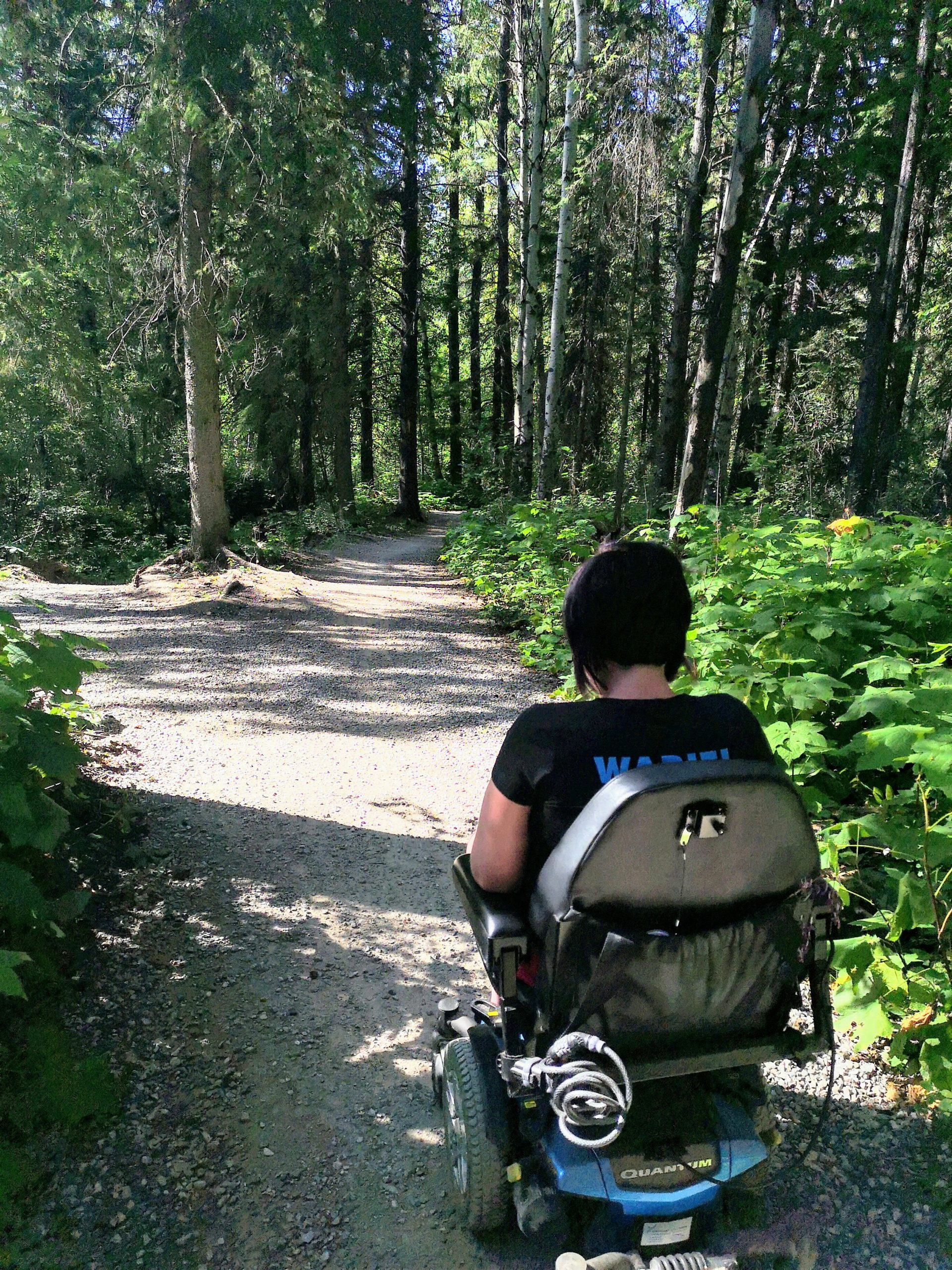 A woman navigates through a forest trail on a moterized chair