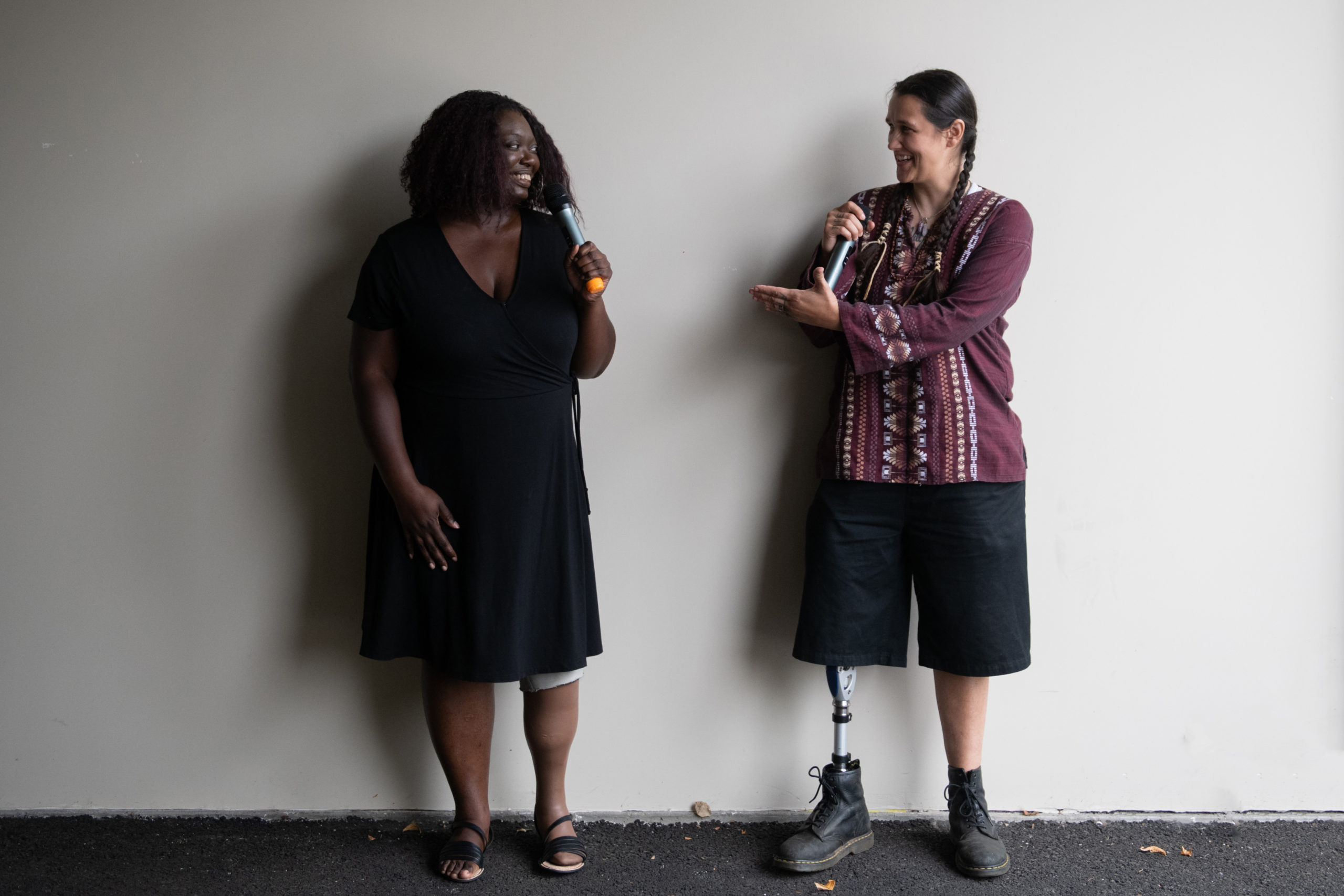 An Indigenous Two-Spirit person and a Black woman face each other and gesture while smiling and speaking into microphones. They are both wearing prosthetic legs.