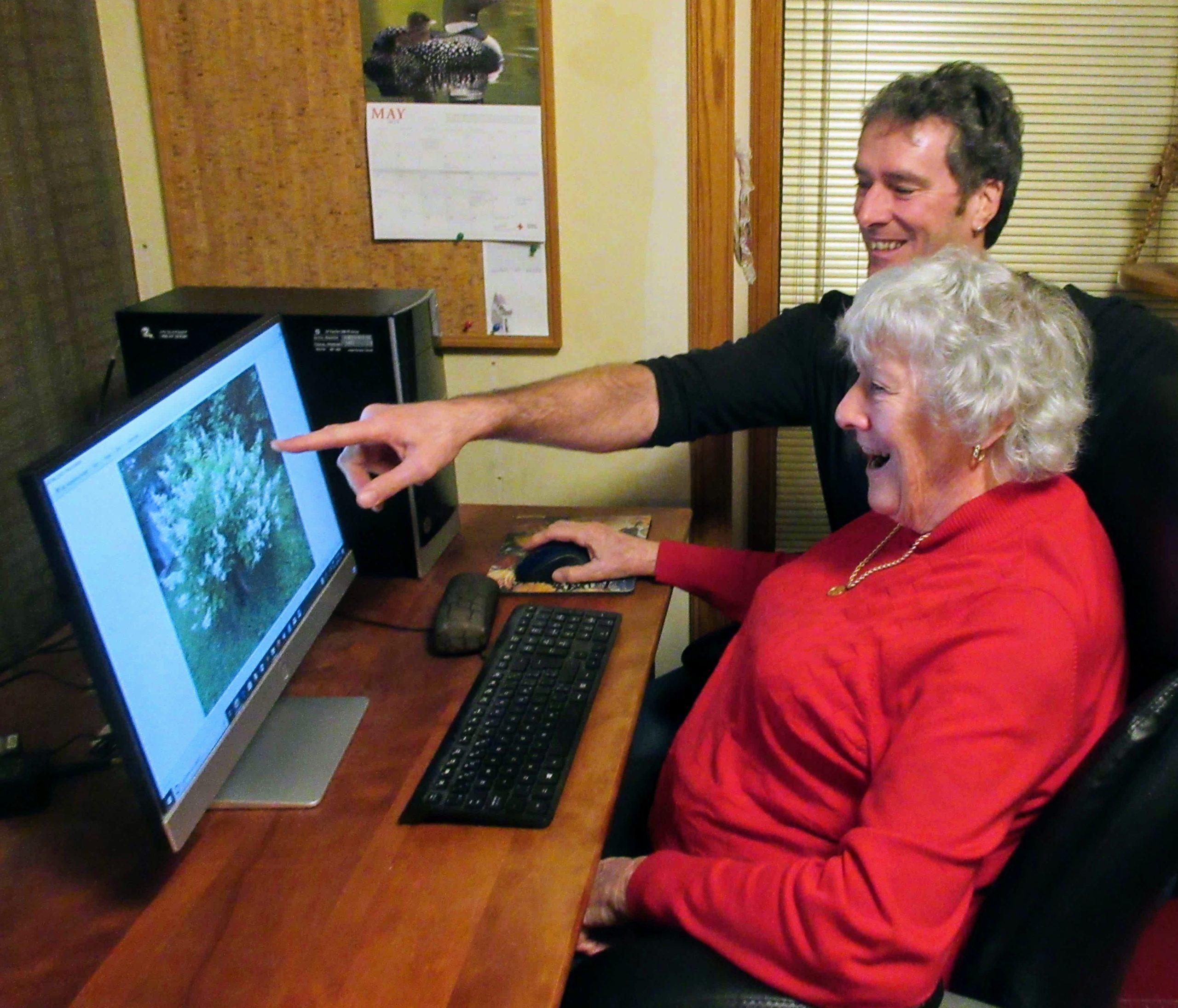 A man teaches an older woman how to use a desktop computer