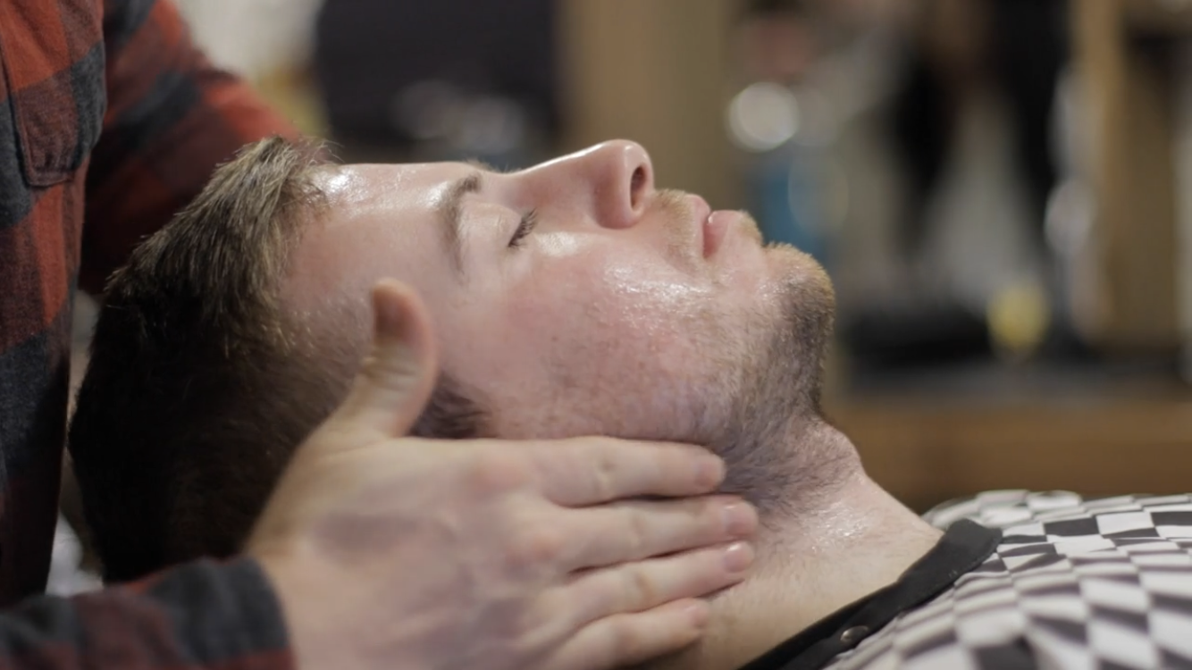 A client lies with their head back while the barber applies pre-shave oil to their facial hair.