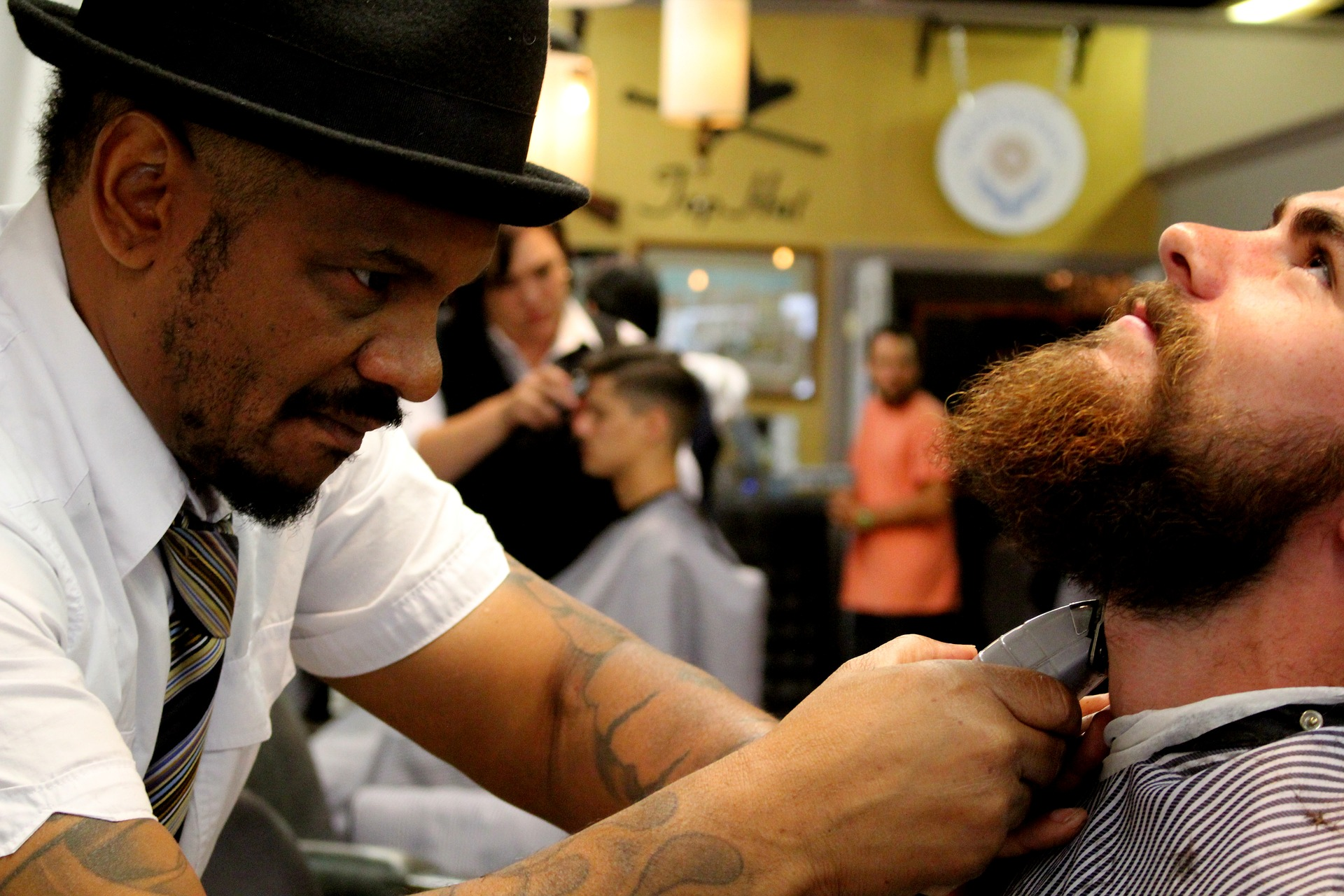 A barber uses a trimmer to outline the edge of a client's beard around their neck.