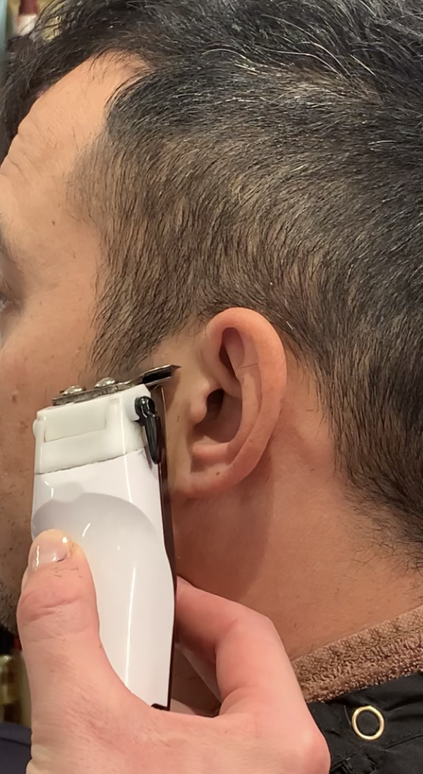 A trimmer is positioned so the teeth point towards the skin to outline the sideburns.