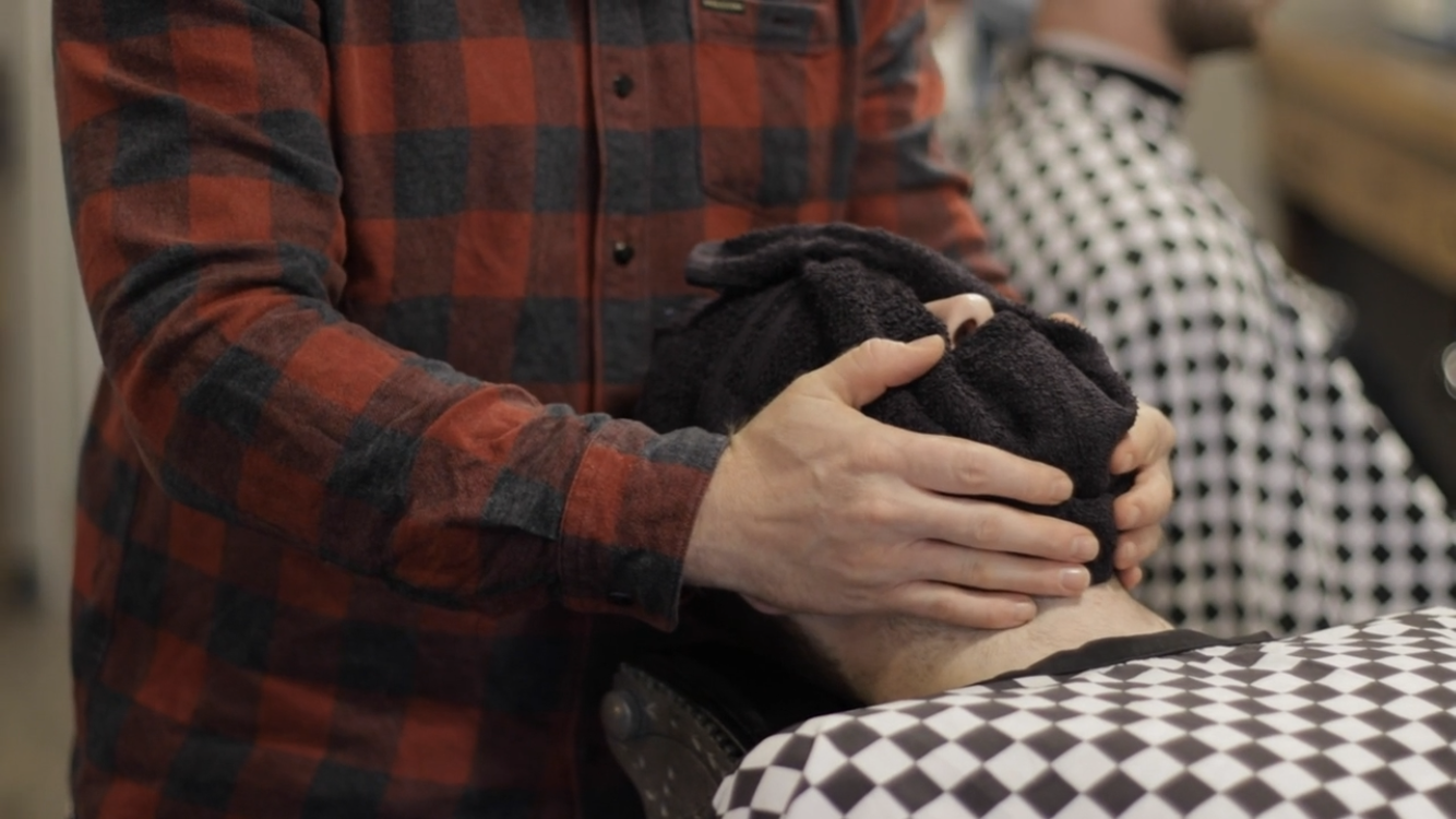 A barber wraps the client's face in a hot towel.