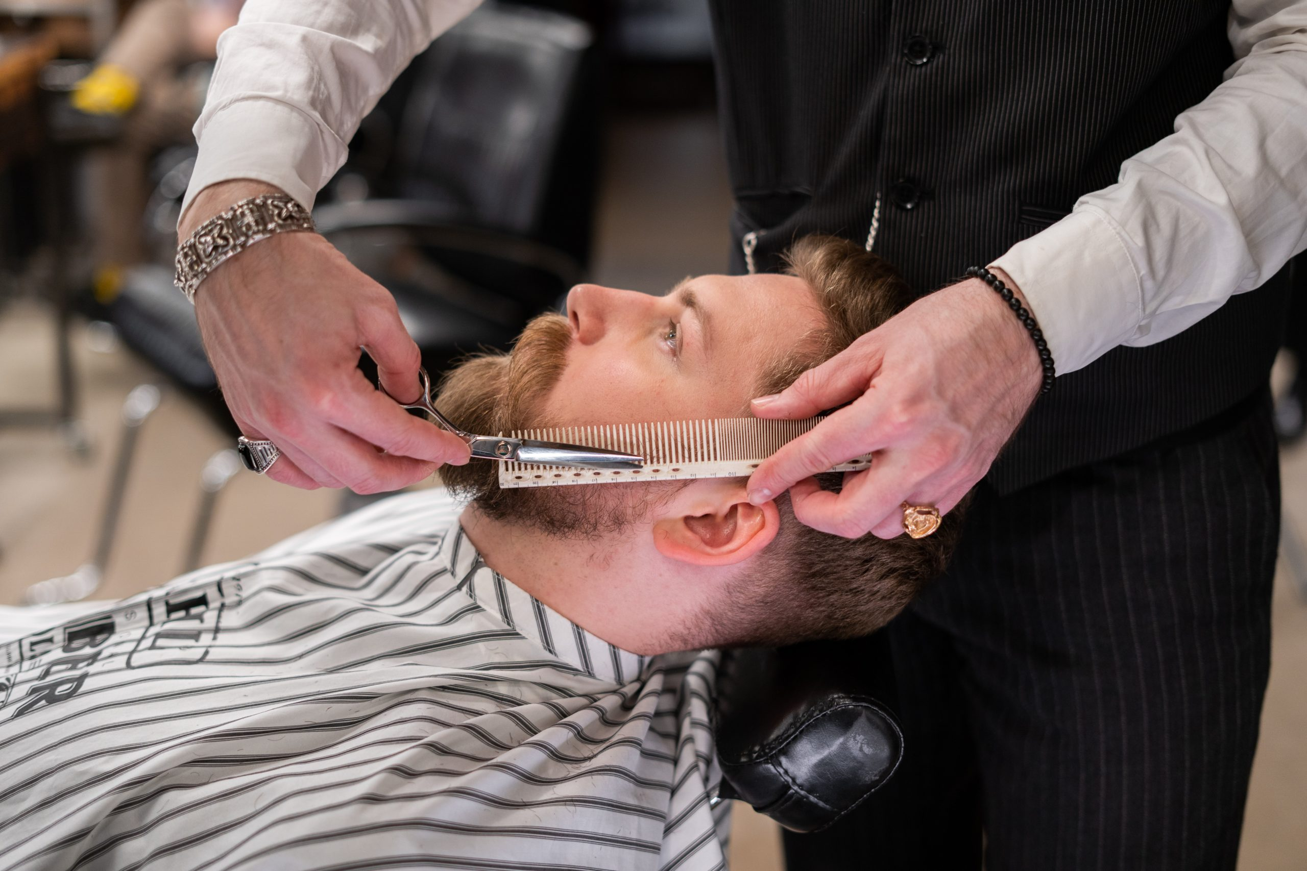 A barber uses the shere-over-comb method to trim a client's beard.