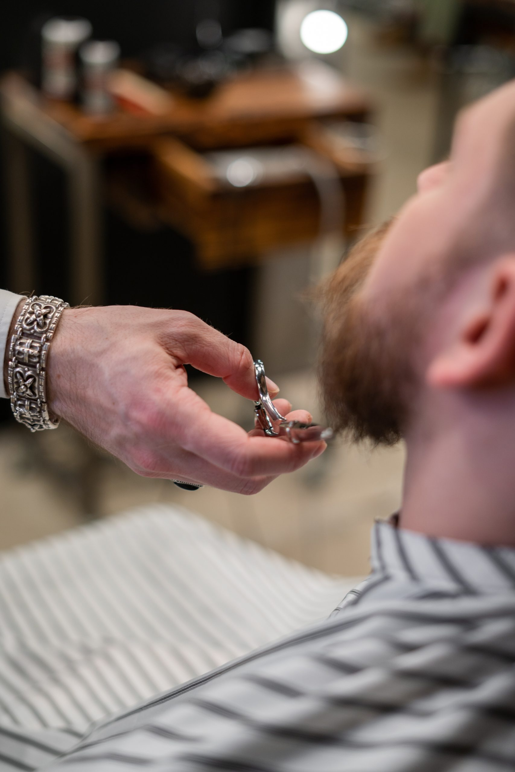 A barber trimming a client's bear with just sheers.