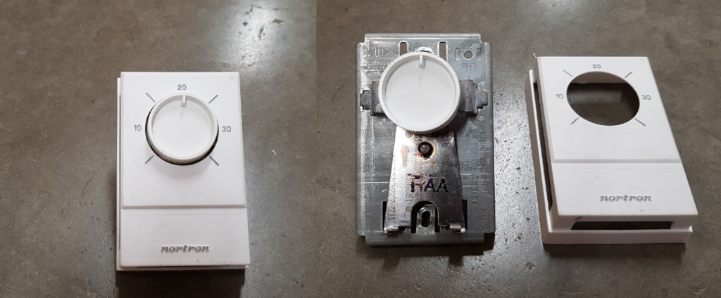 A thermostat that has been taken apart. It has a dial that you use to set the temperature.