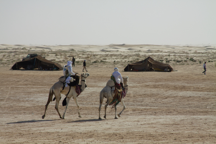 This photo shows two white-clad men riding camels through a sparse desert. Two canvas tents are visible in the background.