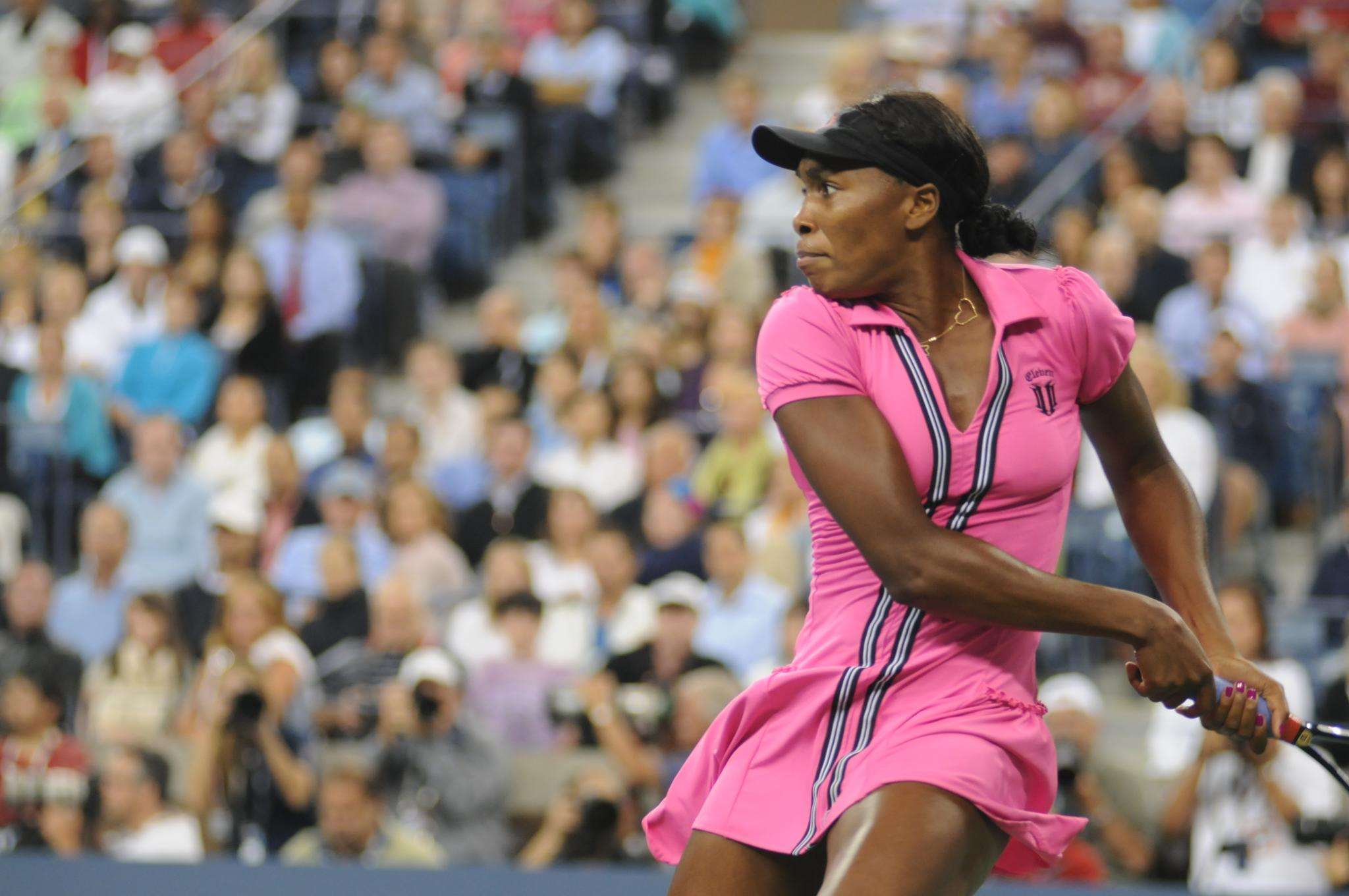 This is a photo of Venus Williams, the famous tennis player, executing a hard tennis swing.