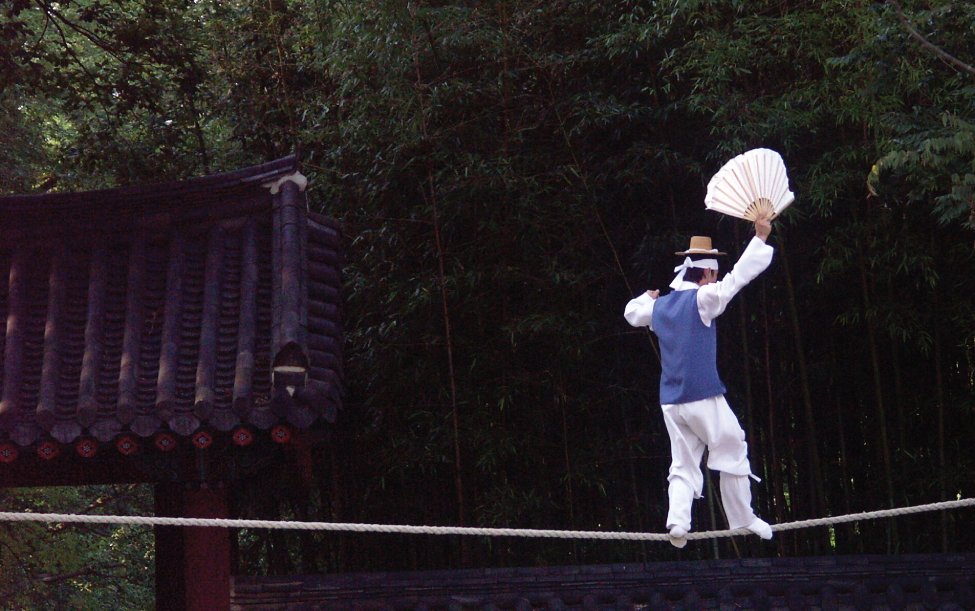 This photograph shows a man balancing on a tightrope.