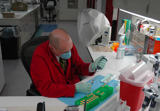 Photo depicts a scientist working in a lab.