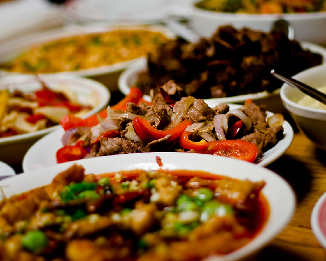 Photo shows plates of food on a dinner table.