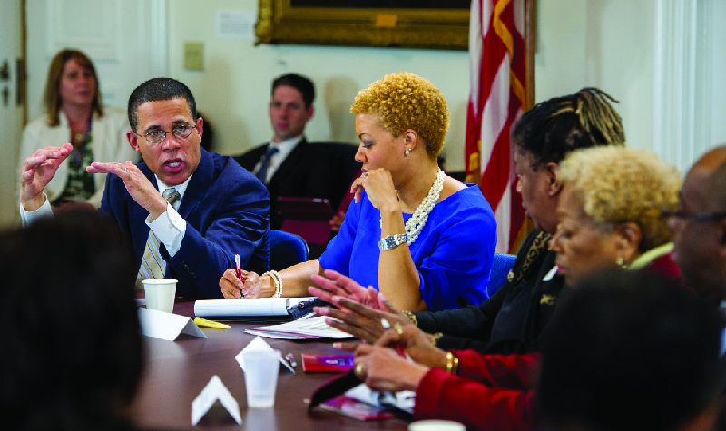This image shows a group of men and women sitting around a table in discussion.