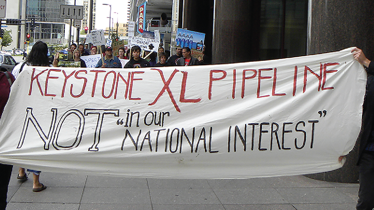 "A banner held by people that reads ""Keystone XL pipeline not in our ""national interest""."""