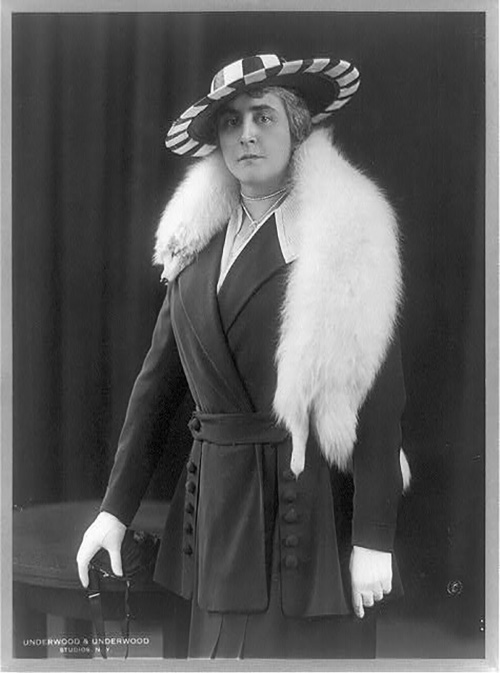 This image shows Anne Morgan wearing a fox stole over her shoulders, gloves, a hat, and a jacket and skirt.