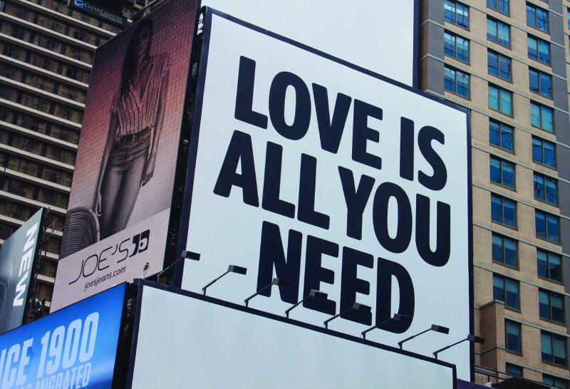 This image shows a billboard on the side of a building that says love is all you need.