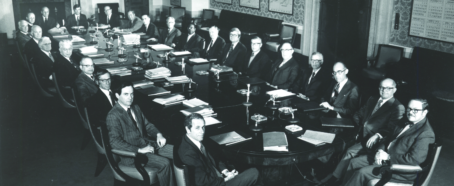 This image shows twenty-three white men and one black man in suits sitting around a large boardroom-style table.