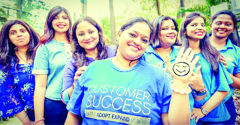 """The image shows seven women smiling. The one in the center is wearing a shirt that says """"Customer Success."""""""