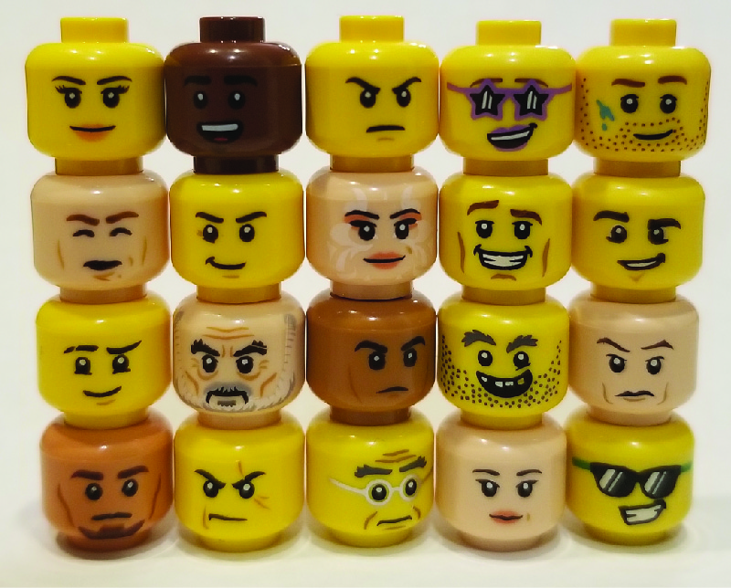 The image shows lego figure heads stacked in five columns, with four heads in each column. The heads show a variety of expressions.