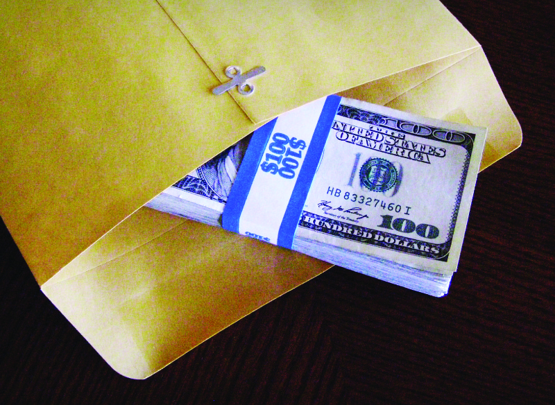 This image shows a stack of 100 dollar bills half in a clasp envelope.
