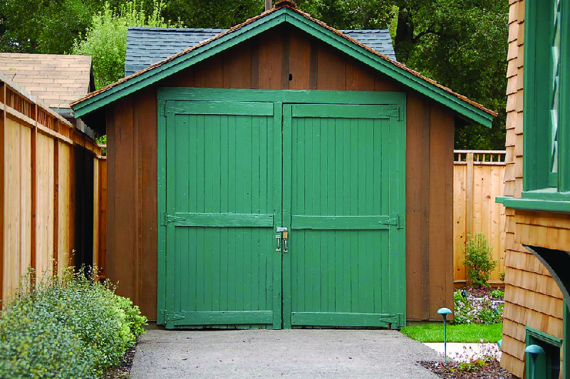 This image shows a small wooden garage in a backyard.