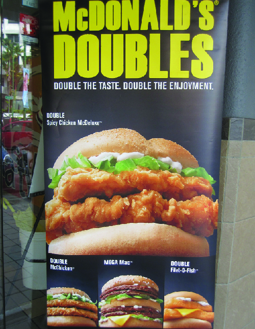 """This image shows an advertisement for McDonald's Doubles. It says """"Double the taste. Double the enjoyment."""" It shows four sandwiches: the Double Spicy Chicken McDeluxe, the Double McChicken, the Mega Mac, and the Double Filet-O-Fish."""