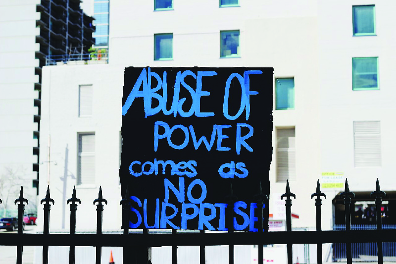 """This image shows a hand-painted sign that says """"Abuse of power comes as no surprise."""""""